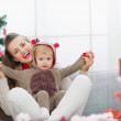 Smiling young mother and baby having fun time on Christmas — Stock Photo