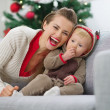 Smiling young mother and baby having fun time on Christmas — Stock Photo #12444478