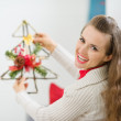 Smiling woman holding Christmas decoration tree — Stock Photo #12444508