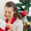 Smiling woman looking into Christmas socks — Stock Photo