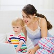 Royalty-Free Stock Photo: Modern young mother and baby using laptop