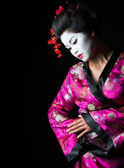 Closeup portrait of geisha isolated on black — Stock Photo