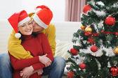 Young man kissing girlfriend near Christmas tree — Stock Photo