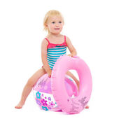 Baby girl in swimsuit with inflatable ring sitting on ball — Stock Photo