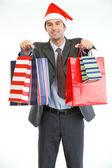 улыбаясь бизнесмен в шапке санта-клауса, показаны сумки для покупок — Стоковое фото