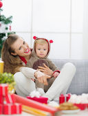Smiling young mother spending Christmas with baby and pointing o — Stock Photo