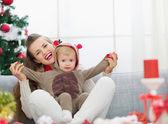 微笑着的年轻妈妈和宝宝很开心时间过圣诞 — 图库照片
