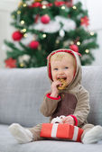 Baby in deer suit with Christmas present box eating cookie — Stock Photo