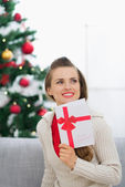 Thoughtful young woman with Christmas postcard — Stock Photo