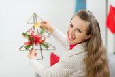 Donna sorridente che tiene l'albero di natale decorazione — Foto Stock