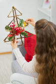 Woman holding Christmas decoration tree. Rear view — Photo