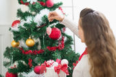 Woman decorating Christmas tree. Rear view — Stock Photo