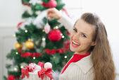 Glückliche junge frau schmücken weihnachtsbaum — Stockfoto