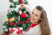 Happy young woman decorating Christmas tree — Stock Photo