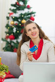 Woman with credit card thinking about Christmas presents — Stock Photo