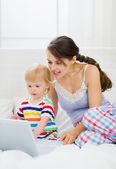 Modern genç anne ve bebek dizüstü kullanarak — Stok fotoğraf