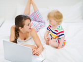 Young mother showing baby something in laptop — Stock Photo