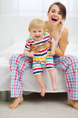 Portrait of happy young mother with baby in bedroom — Stock Photo