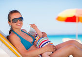 Mother laying on sun bed and holding baby drinking water — Stock Photo
