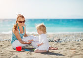 Mother playing with baby on beach — Stock Photo