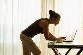 Young woman using laptop leaning against table — ストック写真