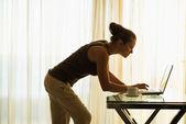 Jonge vrouw met laptop leunend tegen tabel — Stockfoto