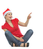 Happy woman in Christmas hat sitting on floor and pointing on co — Stock Photo