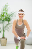 Smiling slim woman making stretching exercises — Stock Photo