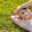 Stock Photo: Young woman relaxing on grass