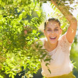 Smiling young woman looking out from foliage — Stock Photo #13725879