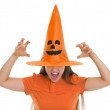 Woman in Halloween hat over eyes making scaring pose - Stock Photo