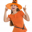 Happy young woman in Halloween hat pointing up — Stock Photo