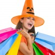Happy young woman in Halloween hat with shopping bags — Stock Photo