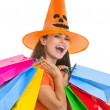 Happy young woman in Halloween hat with shopping bags — Stockfoto