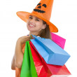 Portrait of happy young woman in Halloween hat with shopping bag — Stock Photo #13728404