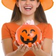 Stock Photo: Closeup on Halloween bucket with sweets in woman hands