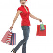 Happy young woman in Christmas hat with shopping bags walking - 图库照片