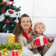 Happy young mother and baby looking on table with Christmas gift — Stock Photo #13729114