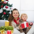 Happy young mother and baby looking on table with Christmas gift — Stock Photo