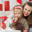 Stock Photo: Smiling young mother and eat smeared baby eating Christmas cooki