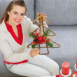 Smiling young woman showing Christmas decorations — Stockfoto
