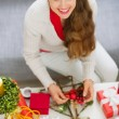 Smiling young woman making Christmas decorations — Stock Photo #13729250