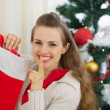 Smiling young woman put gift in Christmas socks and showing shh  — Стоковая фотография