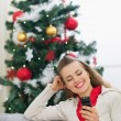Happy young woman writing sms near Christmas tree — Stock Photo #13729317