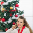 Happy young woman speaking mobile phone near Christmas tree — Stock Photo