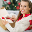 Happy young woman unpacking parcel with Christmas gift — Stock Photo #13729413