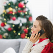 Happy young woman near Christmas tree making phone call — Stock Photo #13729418