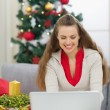 Happy young woman near Christmas tree using laptop — Stock Photo #13729449
