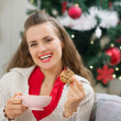 Happy young woman near Christmas tree with cup and cookie — Stock Photo #13729484