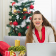 Smiling young woman near Christmas tree sending greeting emails — Stock Photo #13729505